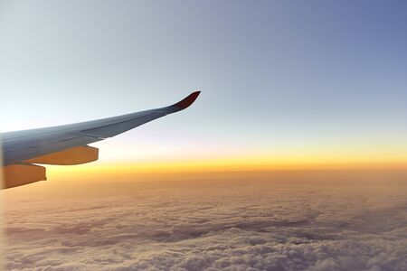 Wing of an aeroplane with sunset sky as seen through window of an aircraft