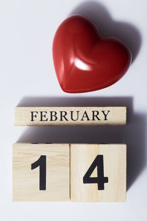 14 February valentine day Red heart shaped with wooden cube calendar with shadow on white background, Flat lay