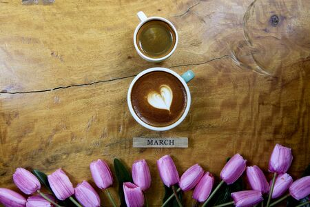 Coffee mug heart shape with tulip bouquet on wooden table for March Greeting card