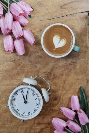 Alarm clock with beautiful bouquet of tulips flower on wooden