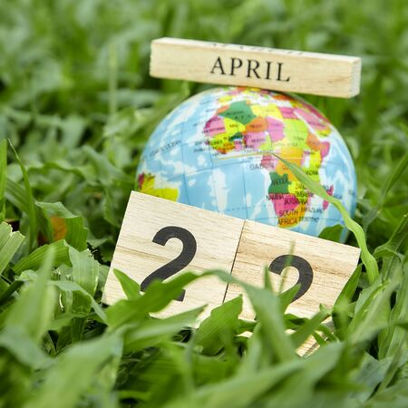 22 April Earth Day Concept, Globe lies on green grass field background textured for banner design
