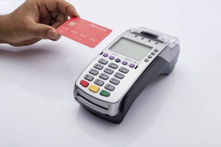 Close up of Male holding in hands wireless modern bank payment terminal to process acquire credit card payments, red card isolated on white background. Copy space for financial advertising