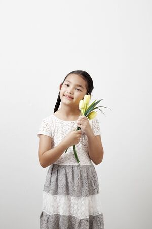 Asian little girl holding a bouquet of yellow tulips on white background. Concept of holidays