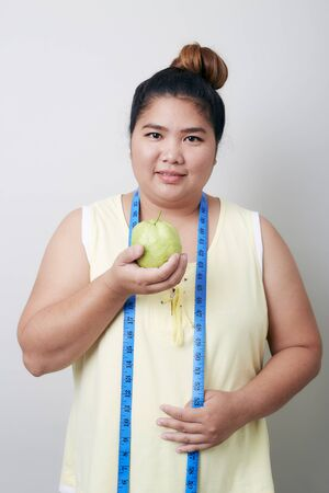 Overweight woman measuring with eating food on  light gray Banner gackground 写真素材