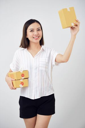 Work from home, Smiling young Thai woman holding small package parcel box on white background, SME business online and delivery concept