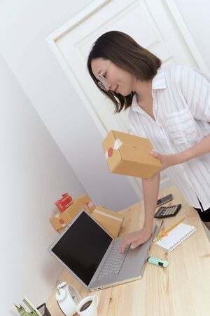 Small business owner work from home, Thai woman checking purchase order in laptop and write in the delivery on package box sell online or online shopping concept