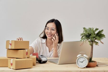 Young attractive asian woman online seller working on laptop computer checking order on internet at home preparing for delivery at from home