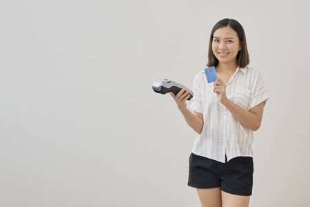 Young smiling beautiful asian woman presenting credit card in hand showing and wireless modern bank payment terminal for making payment