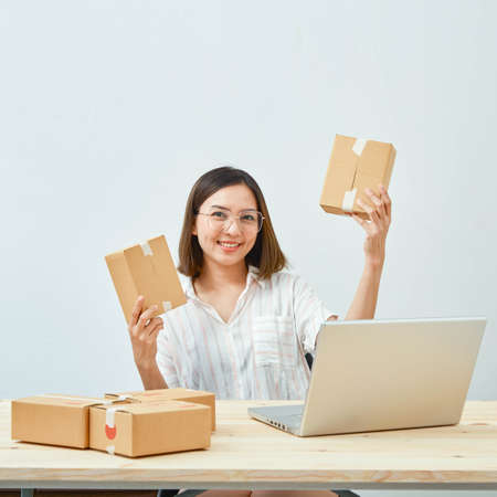 asian girl freelancer business private working at home office with holding tablet, laptop, note, packaging delivery online market on purchase orders to customer Standard-Bild