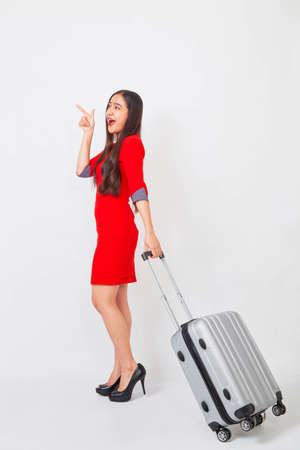 A businesswoman in a red dress with a suitcase on white background, travel concept