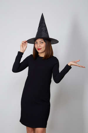 Beautiful asian woman wearing witch costume for Halloween party