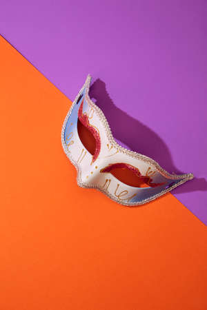 Close up of Mardi Gras or Carnival mask on a bright orange and violet background, Flat lay accessory carnival festival 스톡 콘텐츠 - 154454575