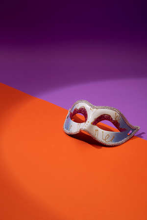Close up of Mardi Gras or Carnival mask on a bright orange and violet background, Flat lay accessory carnival festival