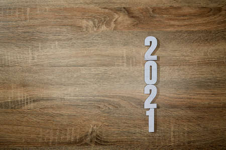 wooden white numbers 2021 on Wooden desk background. change year 2020 to 2021