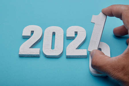 Flat lay Numbers 2021 and hand on pastel blue  background for Christmas or New Year