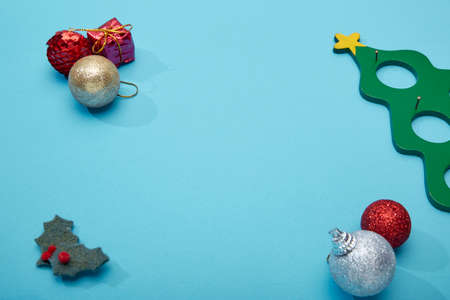 Top view Christmas and New Year holiday ball decorations and toys on blue background