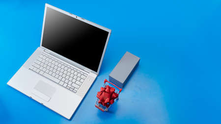 Top view Blank laptop with red bow in Shopping cart and blank gift box on violet background for Christmas Sale