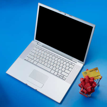 Top view Blank laptop with Credit card and red bow in Shopping cart and blank gift box on violet background for Christmas Sale