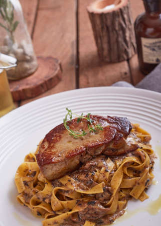 Grilled Foie gras steak with with Fettuccine pasta on restaurant table