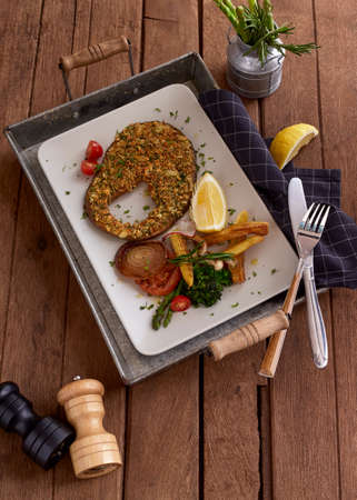 Tasty grilled salmon steak with lemon and herbs on table rustic wooden background Archivio Fotografico