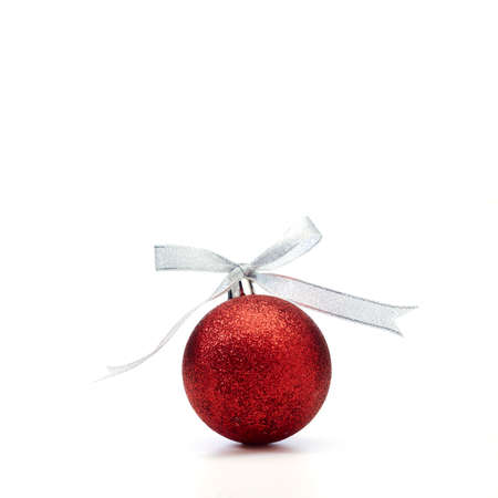 Red Christmas ball with silver ribbon on white background Archivio Fotografico