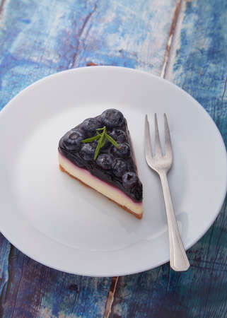 Piece of blueberry cheese cake on white plate on wood background