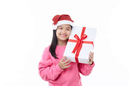 Cheered and happy Christmas Asian girl wearing a Santa hat hugging gift box in the hands isolated over a white background