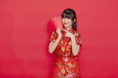 Portrait beautiful young Asian Cute woman wear Chinese dress with Ang Pao or red letter with cash for Chinese new year concept on red isolated background