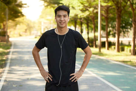 Young handsome Asian man exercising outdoors listening to music in the park. Stock fotó