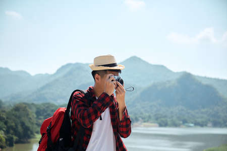 Young hipster Asian man traveling with a backpack in summer forest trip travel lifestyle concept