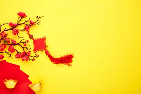 Chinese New Year 2021 Red Chinese knot with flowers and red envelopes on a yellow background copy space for text