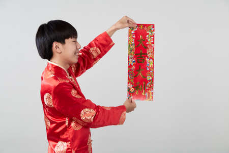 Asian man in traditional oriental costume holding couplet the Chinese word means congratulations and best wishes for a prosperous on light gray background for Chinese new year concepts