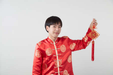 Portrait of Oriental young man with traditional clothing holding Chinese lucky word the Chinese word means congratulations and best wishes for a prosperous on light gray background for Chinese new year concepts