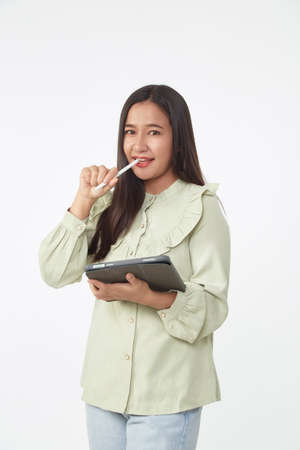 Wireless technology. Beautiful young Asian woman holding digital tablet and looking at camera with smile while standing isolated on white background.