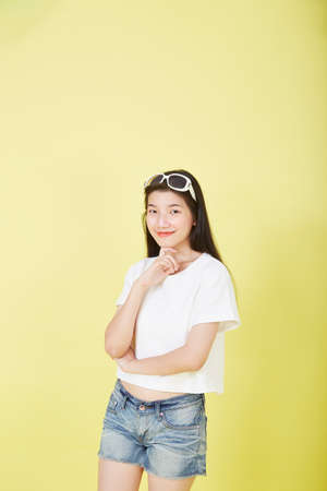 Close up Portrait of the beautiful Asian young brunette woman thinking on the yellow background