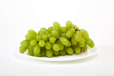 ripe green grapes on a white plate isolated on white background
