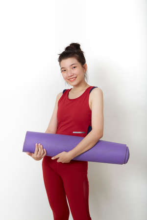 exercise fitness Thai Asian woman ready for workout standing holding yoga mat on white background