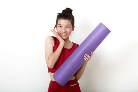 Asian woman ready for workout standing holding yoga mat on white background