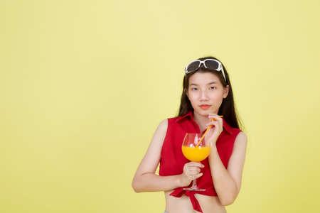 Portrait of a beautiful young Asian woman drinking orange juice Reklamní fotografie