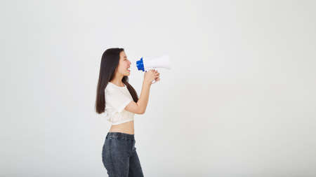 cheerful young Asian woman holding megaphone announcement in isolated studio
