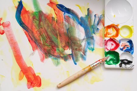 A brush put on the color palette. A child paint with colorful watercolor on the white painting paper.