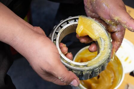 An Asia man putting lithium grease EP (extreme pressure) NLGI 3 into wheel bearing for ten wheel track by hand in the garage. Industrial and automotive concept