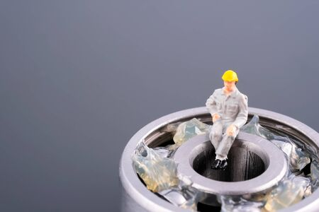 Miniature people : Engineer man sitting on the ball bearing. Ball bearing was putted with lithium grease (NLGI 3). Industrial and business concept