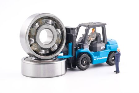Miniature People : Business man see engineer driving forklift and lift up ball bearing which have Lithium grease (NLGI 3) isolated on white background. Industrial and business concept.