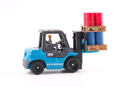 Miniature People : Engineer driving forklift and lift up palette which have four red drums and four blue drums isolated on white background. Industrial and business concept. Reklamní fotografie