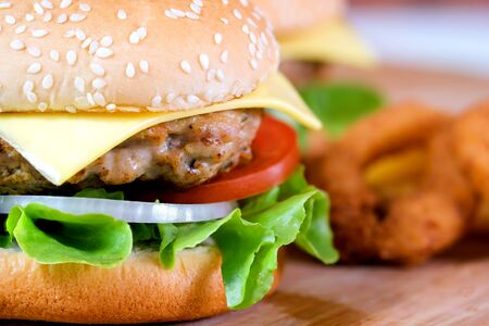 Close-up macro of delicious fresh homemade hamburger with cheese, pork, tomato, onion and vegetable on a wooden plate with french fries and onion ring. Foto de archivo