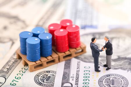 Miniature people : Business man standing in front of drums (oil) and shake hand with team. Oil trend down. The background is US dollar. Price oil down. Barrel arrow down. Business and finance concept.