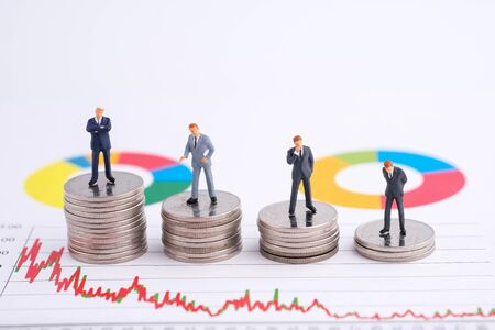 Miniature people:Businessman teams standing on coin with copy space. Financial crisis. Data analysis. Stock market volatility risk. Information for investment. Financial concept