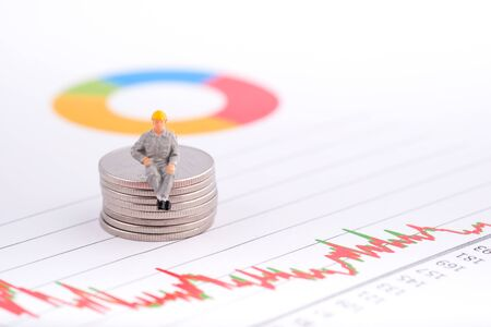Miniature people:Engineer sitting on coin with copy space. Financial crisis. Data analysis. Stock market volatility risk. Information for investment. Financial concept
