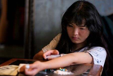 Young Asia woman sitting in the abandoned house and feeling hopeless. There are many drug and gun on the table. A girls used syringe to input drug at her arm. Drug addict and hopeless concept